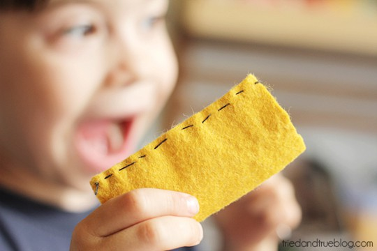 Child holding sewn piece of felt with pride.