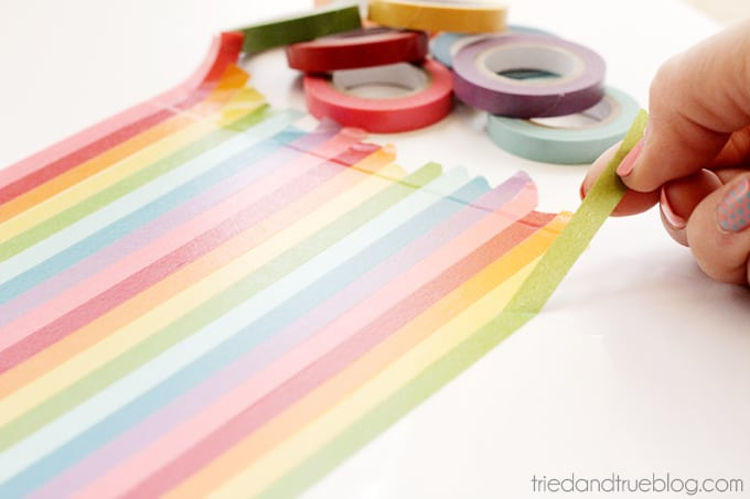 Hand placing rainbow of thin washi tape on paper.
