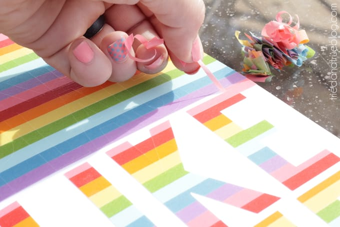 Hand peeling up the excess washi tape.