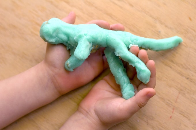 Hand holding dinosaur skeleton covered in dough.