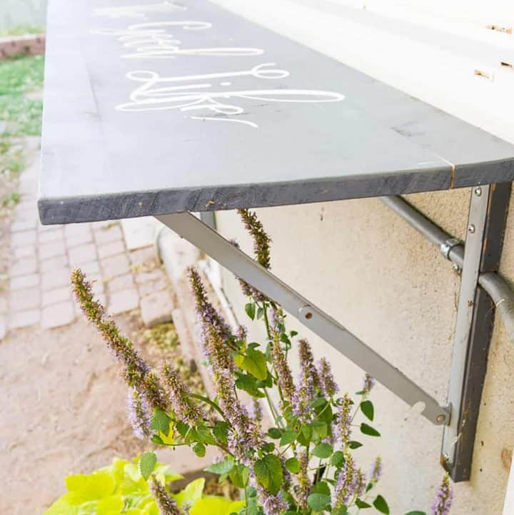 Outdoor folding bar shelf on a house wall with plants growing under.