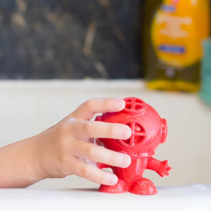 Hand grabbing red soft toy out of bath tub.