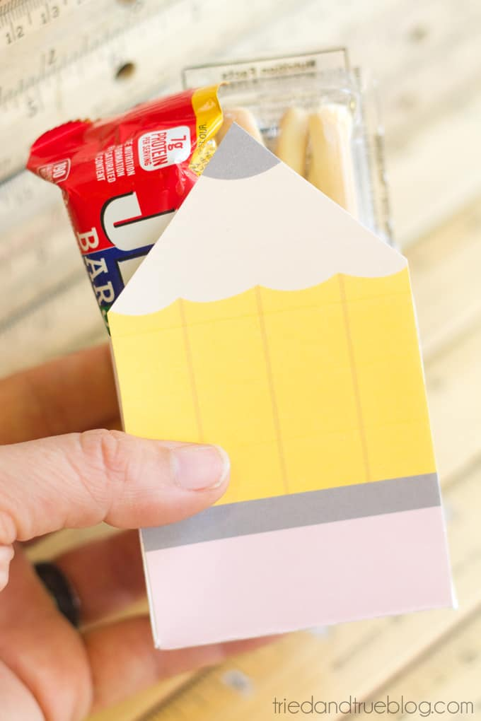 Hand holding a printed gift box in the shape of a pencil with snacks inside.