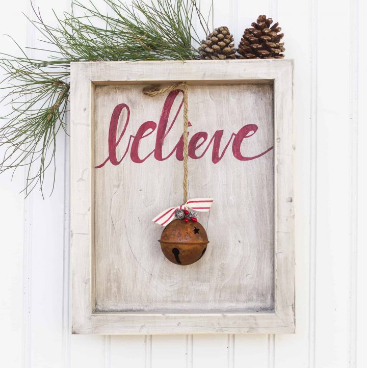 """Rustic wood frame with the word """"believe"""" and old bell."""