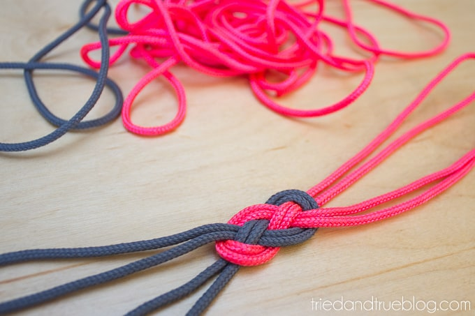 Pink and gray cording tied in knot.