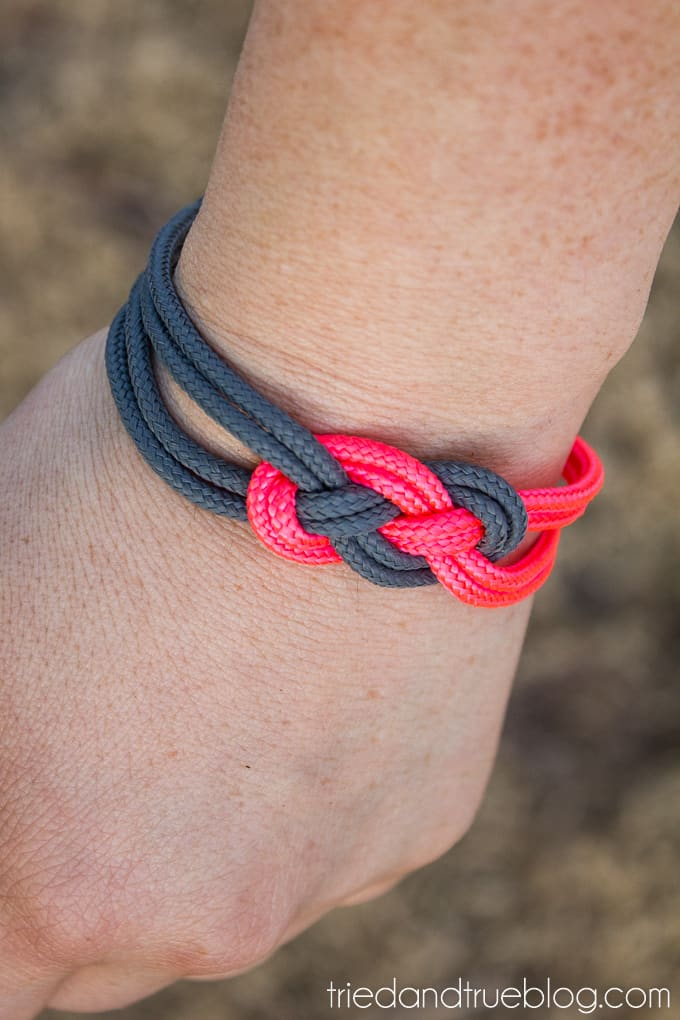 Wrist with pink and gray sailor knot bracelet.