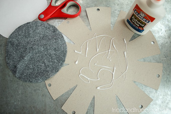 Felt circle being glued onto the bottom of the cardboard template.