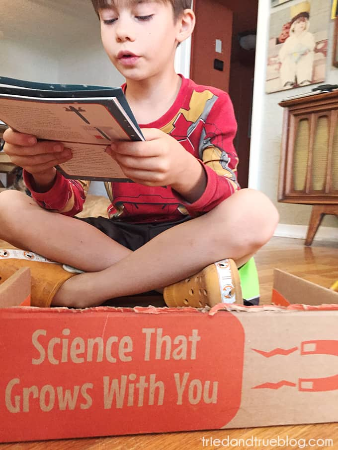 Child reading manual from the  Groovy Lab In A Box STEM subscription boxes.
