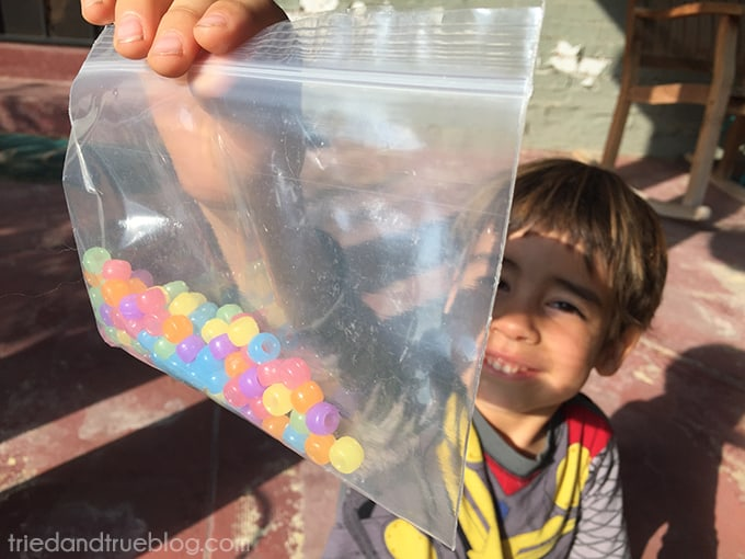 Child holding UV sensitive beads up to the sun.