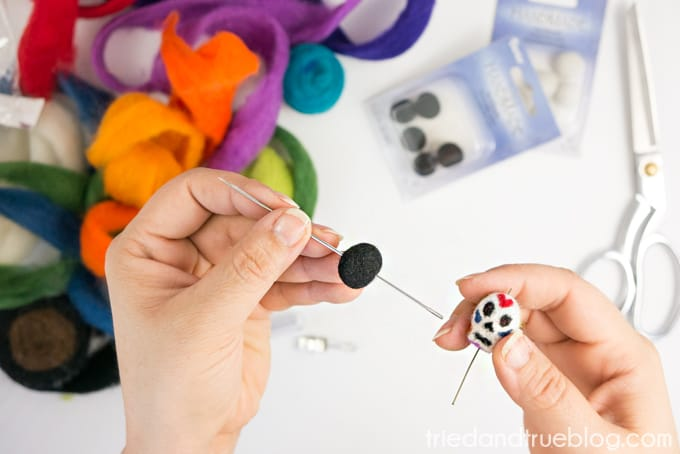 Use long needle to thread wool ball and skull onto eye hook