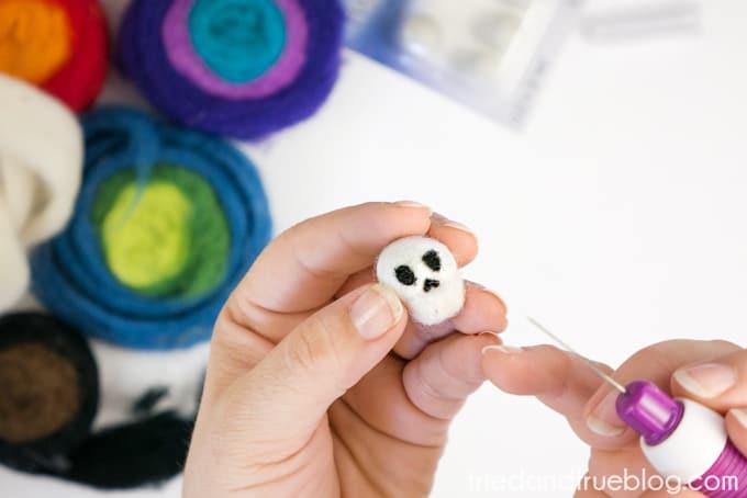 Adding black wool to white wool ball to make skeleton nose
