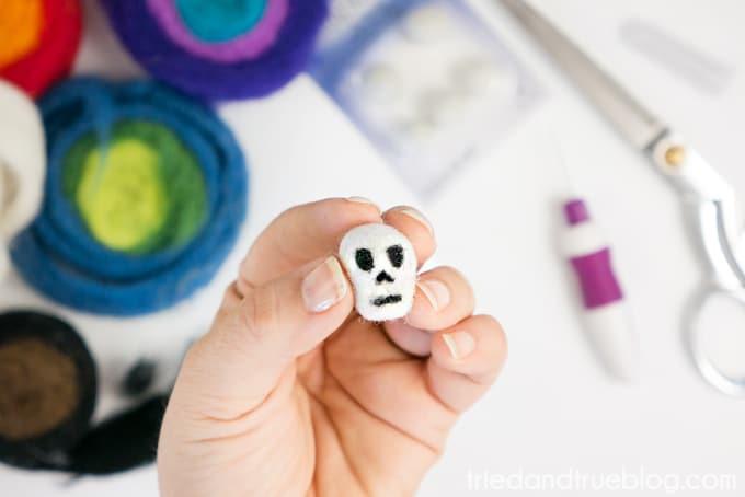 Adding black felt to white wool to make skeleton mouth