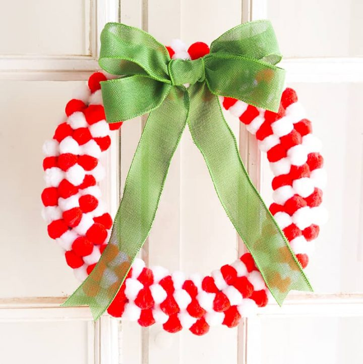 Red and white pom pom wreath on a door with green bow