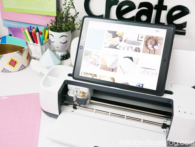 Cricut Maker on a desk with supplies and iPad.