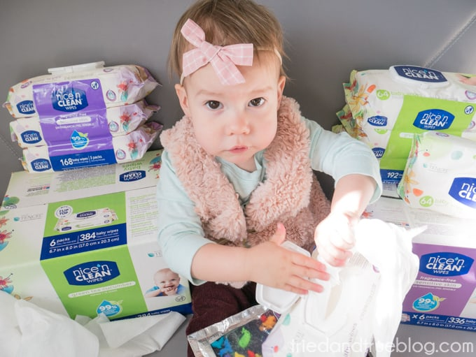 Baby holding diaper wipes while waiting for diaper change.