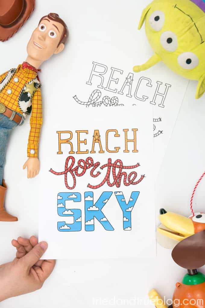 """Toys surrounding hand holding Toy Story """"Reach for the Sky"""" free printable."""