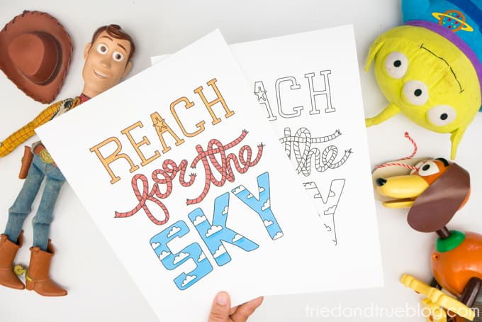 """Hand holding two Toy Story """"Reach for the Sky"""" Free Printables surrounded by toys."""