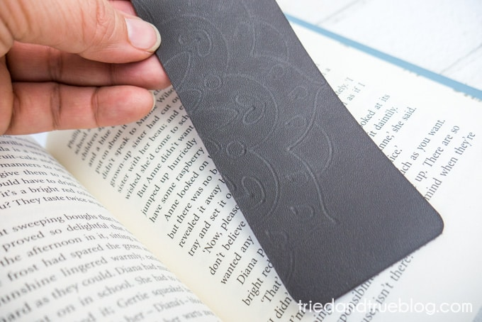 Close up of hand holding a Mandala Debossed Leather Bookmark.