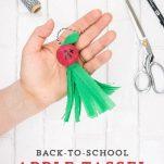 Hand holding Teacher Apple Tassel.