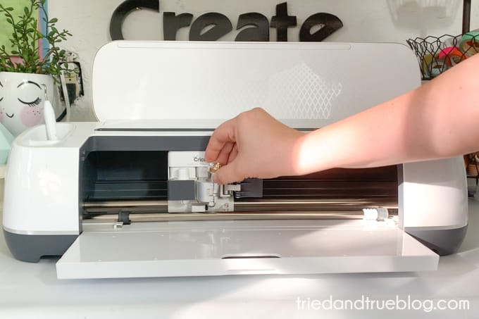 Hand inserting embossing tool into a Cricut Maker.