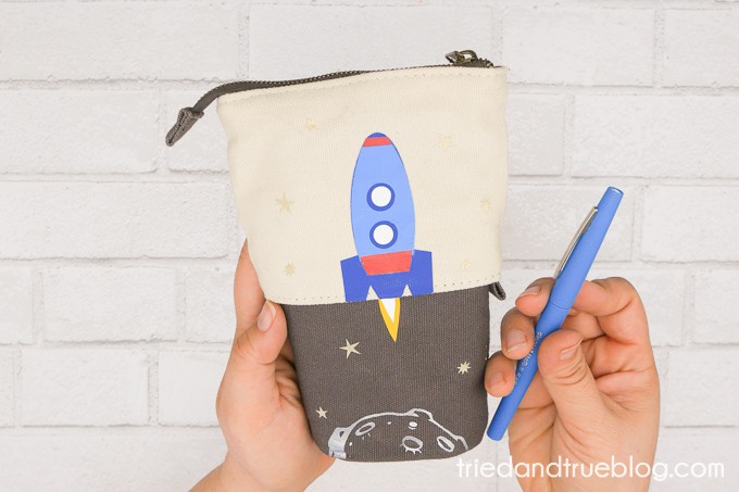Hands holding Collapsible Pencil Case with a blue pen and ready for back to school.
