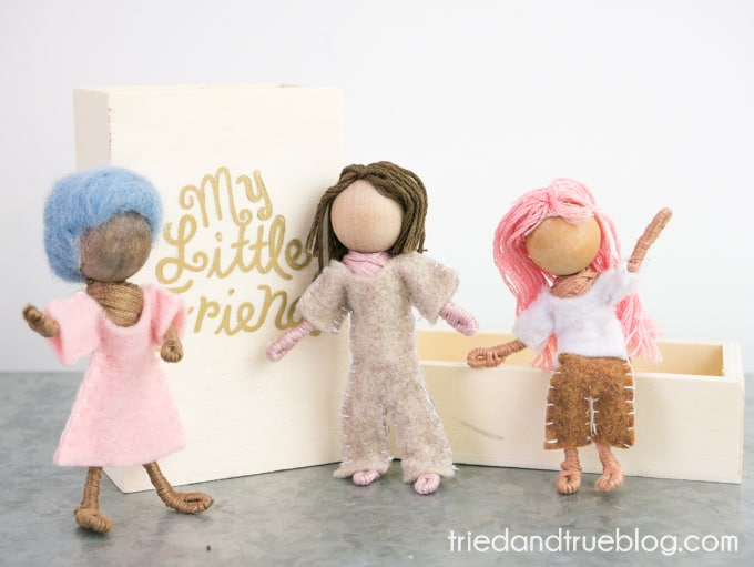 Three little pipecleaner dolls set up around a wood matchbox.