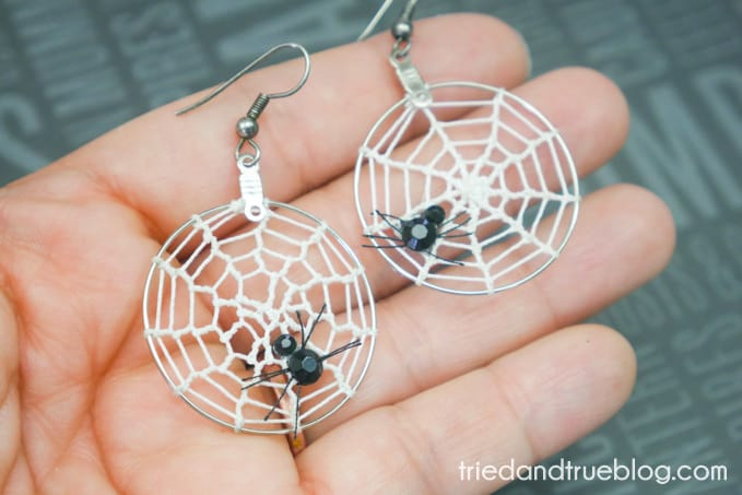 Hand holding hoop earrings with spider web crocheted in them.