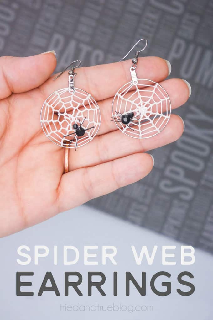 Hand holding Halloween Spider Web Earrins (silver hoop earrings with spider web crochet and rhinestone spiders).