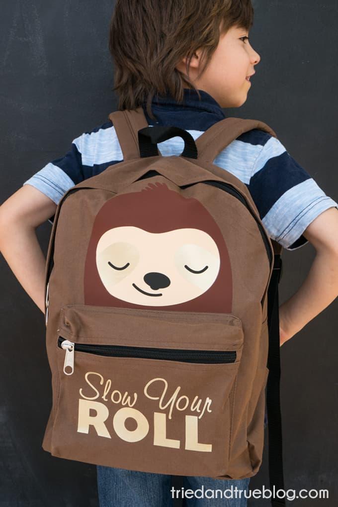 Little boy wearing the DIY Vinyl Sloth Backpack.