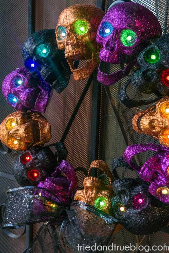 Close up of Dollar Store Halloween Skull Wreath with lights shining in eyes.