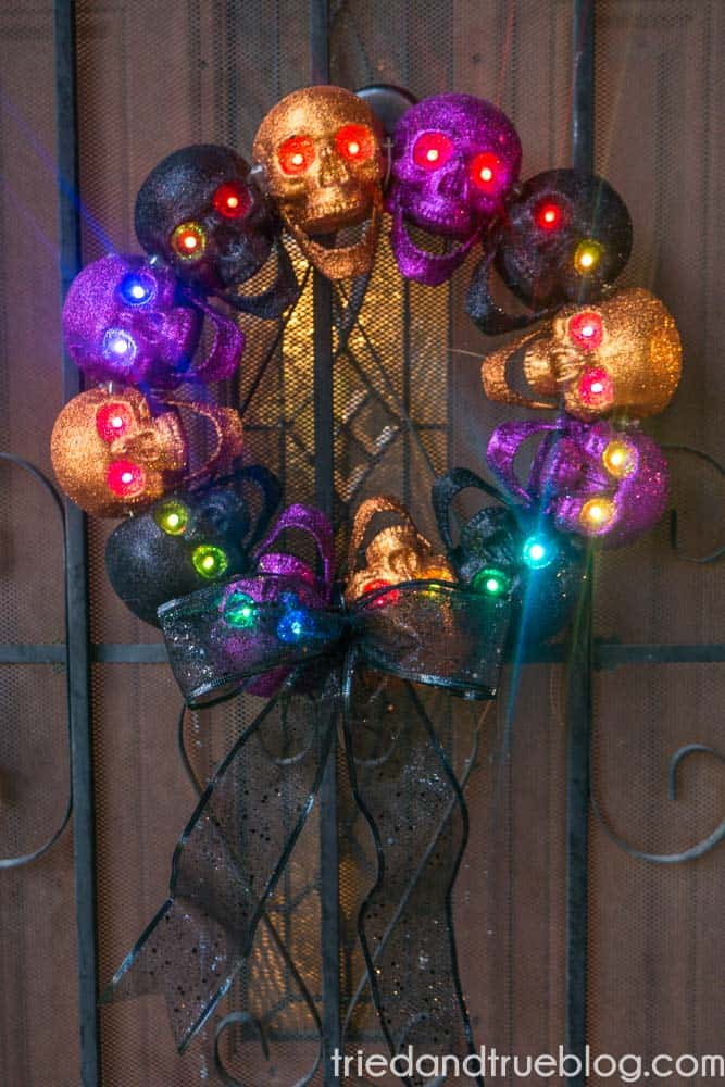 Metal door with a dollar store wreath made of glitter purple, orange, and black skulls. Eyes have different colors of lights shining.