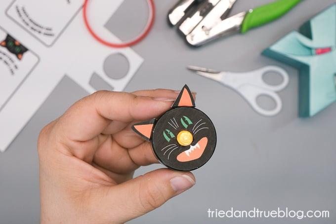 Hand holding an assembled Black Cat Tea Light.