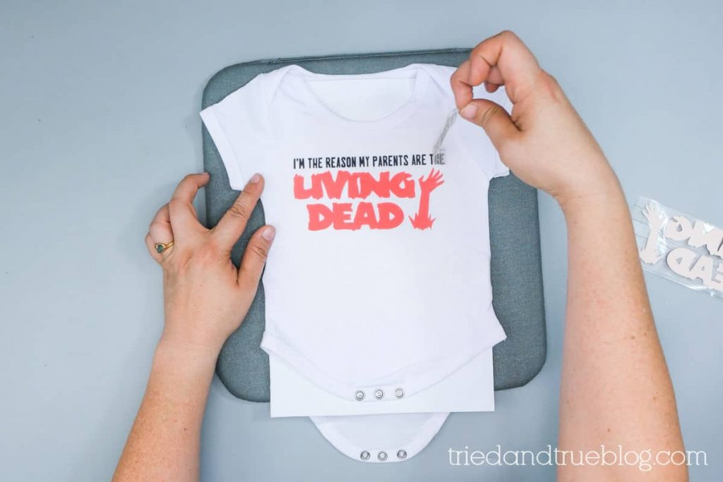 Peeling Infusible Ink transfer paper off a baby onesie.