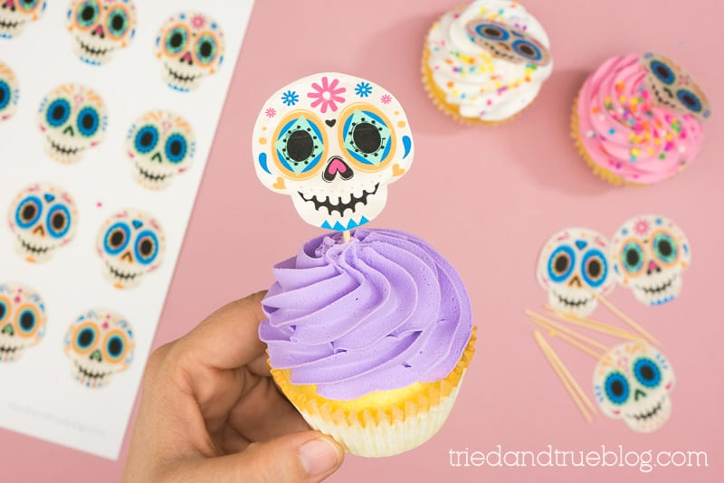Hand holding purple cupcake with Sugar Skull Topper.