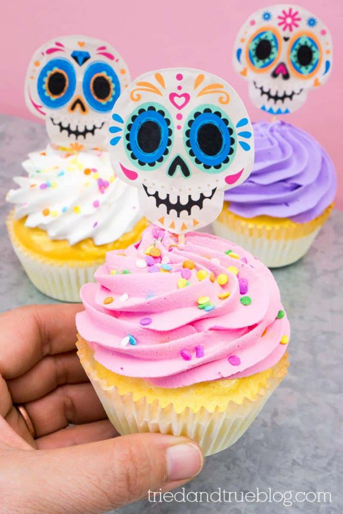 Hand holding pink frosted cupcake with Day of the Dead (Dia de los Muertos) Sugar Skull Cupcake Topper.