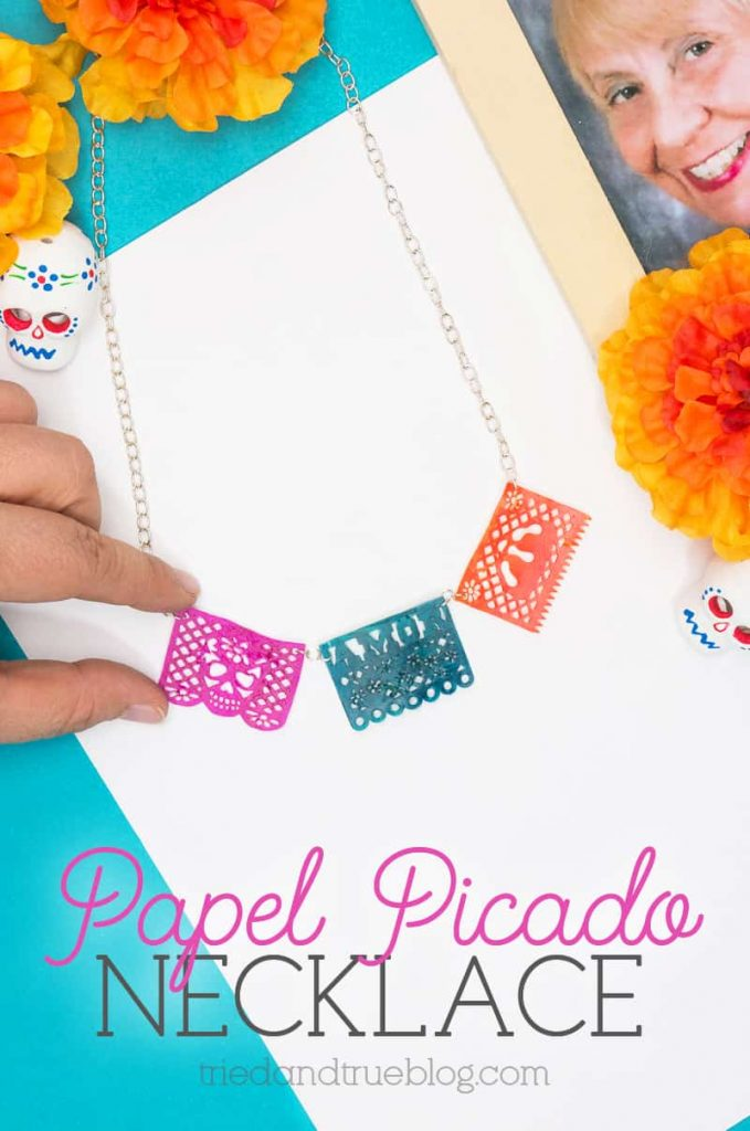 Hand holding Dia de los Muertos Papel Picado Necklace surrounded by holiday artifacts.