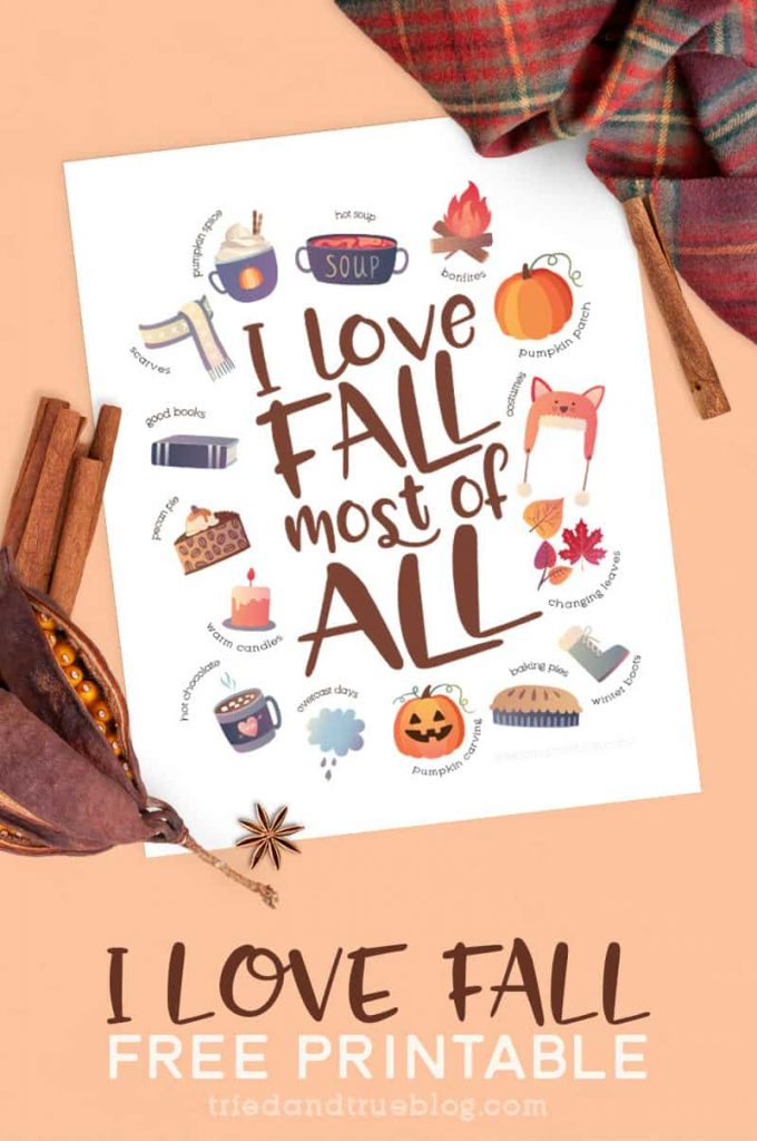 """""""I Love Fall"""" Autumn Free Printable on a piece of paper surrounded by scarf, cinnamon sticks, and other autumn artifacts."""