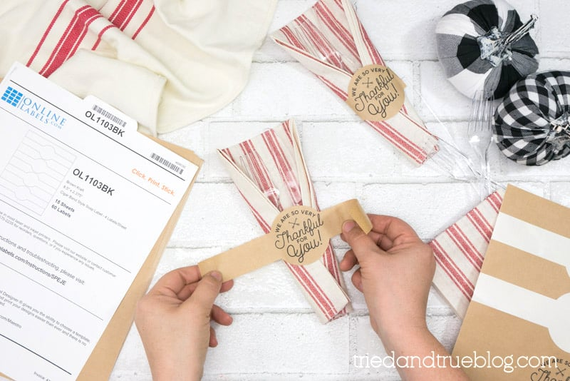 Hands wrapping a napkin and utensils in a Thanksgiving label.