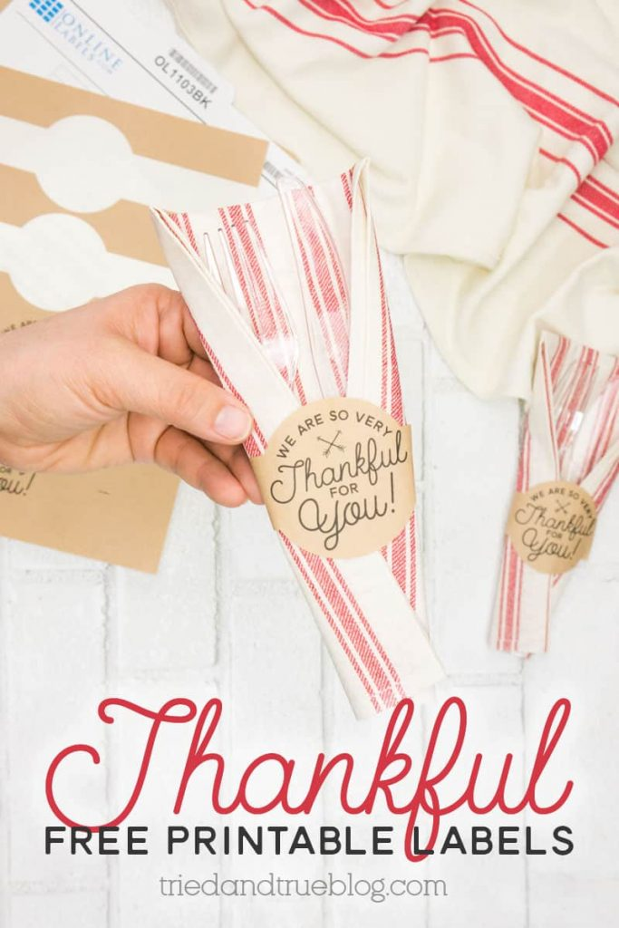 Hand holding napkin and utensils wrapped in the Thanksgiving Free Printable Label.
