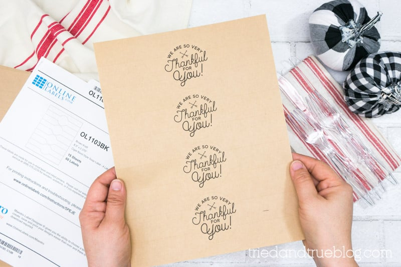 Hands holding a sheet of Thanksgiving Free Printable Labels.