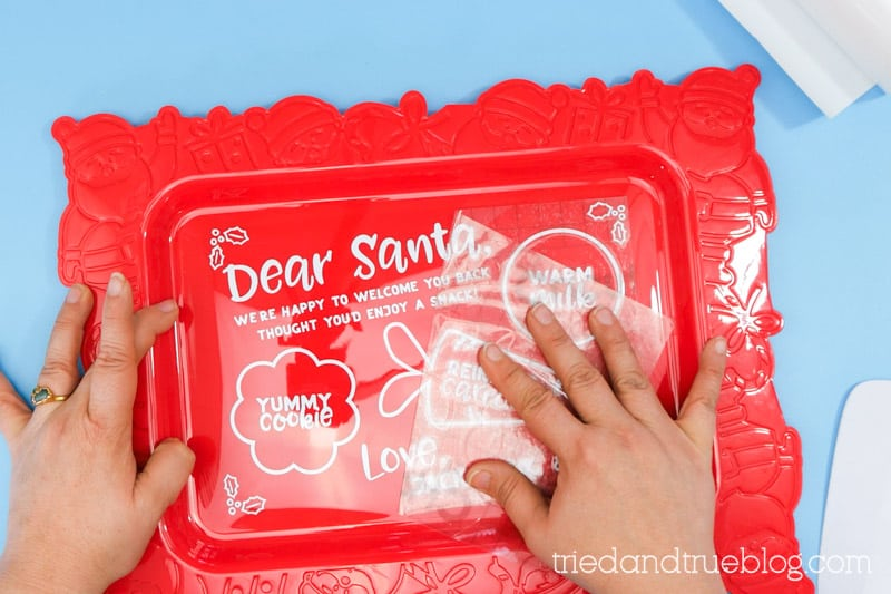 Hand pulling transfer tape off of the Dear Santa Snack Tray.