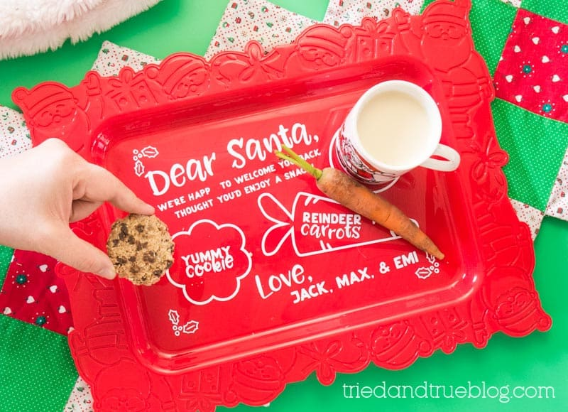 Hand placing a cookie on the Dear Santa Snack Tray.