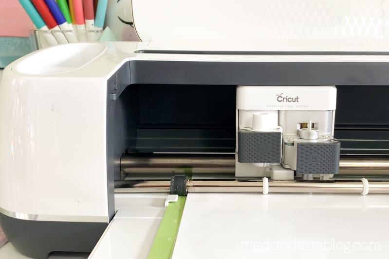 Cricut machine cutting white vinyl.