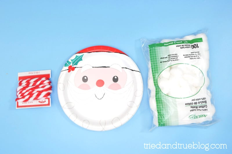 Supplies needed to make a Christmas Countdown for kids: cotton balls, santa plate, and ribbon.