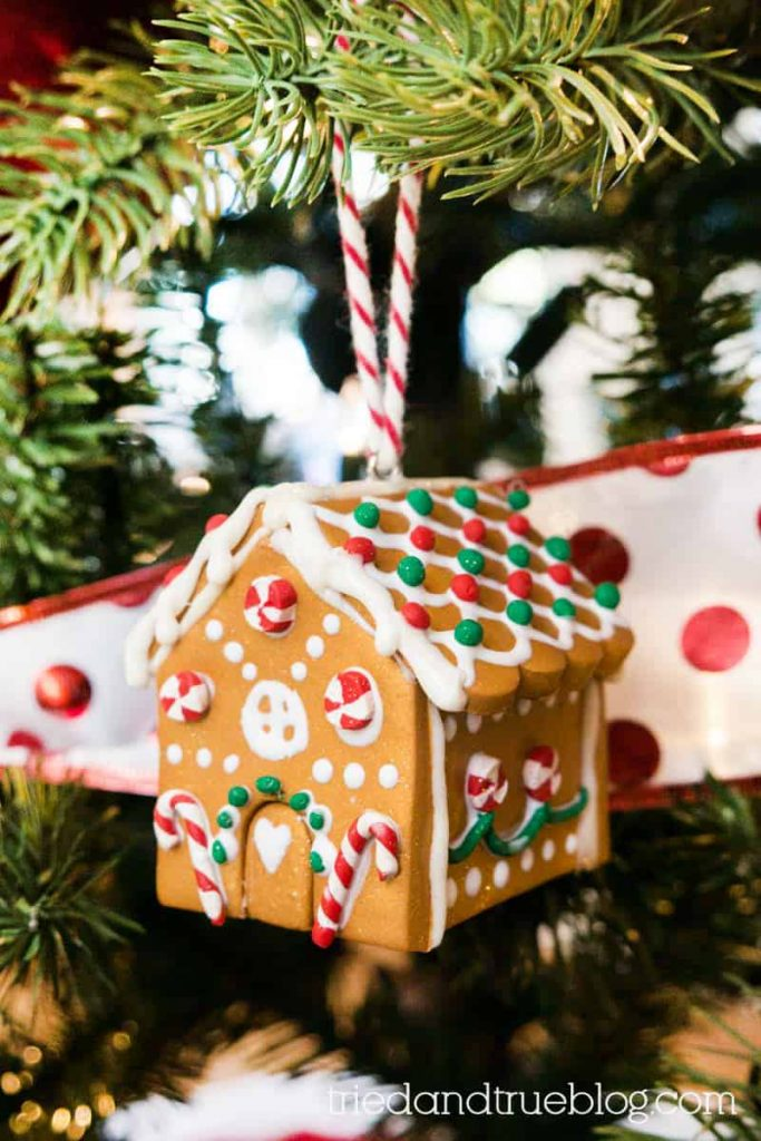 Handmade clay gingerbread house hanging on a lighted tree.