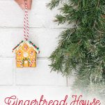 Hand holding gingerbread ornament about to hang on tree.