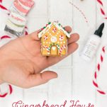 Hand holding Gingerbread House Homemade Clay Ornament in front the supplies.