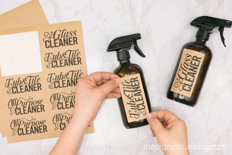Hands place free Cleaner Bottle labels on amber glass bottles.