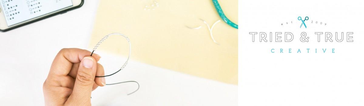 Hand holding handmade Morse Code Bracelet.