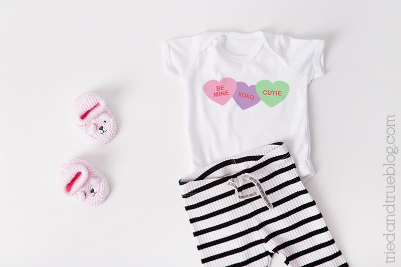 Baby onesie with Conversation Hearts on it.